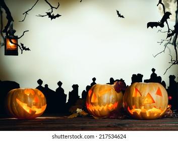 Halloween pumpkin on wooden planks. Cemetery grave stones on background