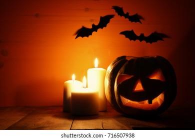 Halloween Pumpkin on wooden table in front of spooky dark background. Jack o lantern.