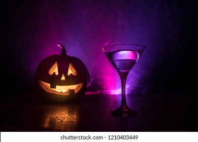 Halloween pumpkin orange cocktails. Festive drink. Halloween party. Funny Pumpkin with a glowing cocktail glass on a dark toned foggy background. Selective focus