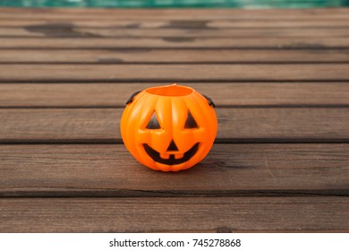 Halloween pumpkin, orange plastic happy or smiling Jack-O'-Lantern bucket toy on wooden ground floor