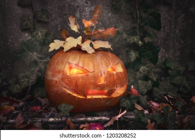 Halloween pumpkin outdoors with candle inside and ivy leaves around