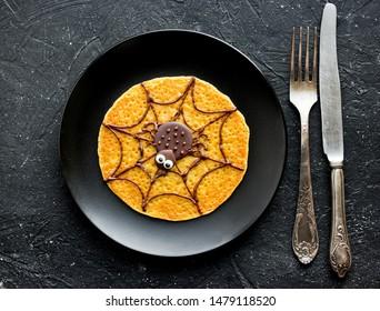 Halloween pumpkin pancake with chocolate spider for funny kids breakfast