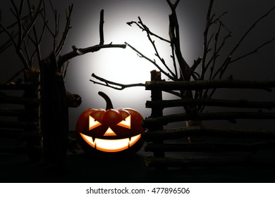 Halloween pumpkin with scary face beside an old wooden fence