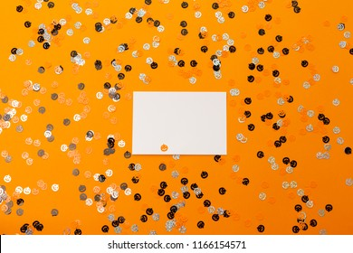 Halloween pumpkin shape colorful confetti on the bright orange background.Flat-lay, top view.