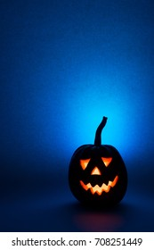Halloween pumpkin, silhouette of funny face on blue background.