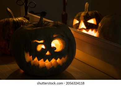 Halloween pumpkin smile and scary eyes for party night with reflection. Close up view of scary Halloween pumpkin with eyes glowing inside at dark background. Selective focus