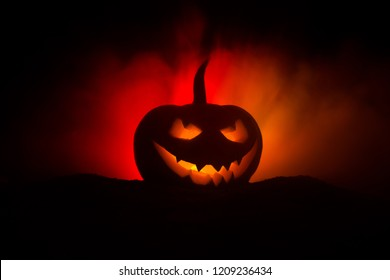 Halloween pumpkin smile and scrary eyes for party night. Close up view of scary Halloween pumpkin with eyes glowing inside at black background. Selective focus