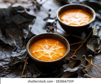 Halloween pumpkin soup with creamy spider web in black bowls on a dark background close up view