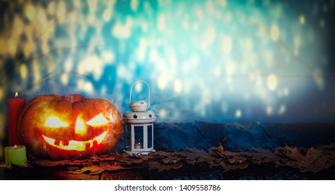 Halloween pumpkin in a spooky forest on the boards with burning candles, mystical landscape. Copy space.