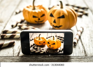 Halloween pumpkin with take picture in mobile phone