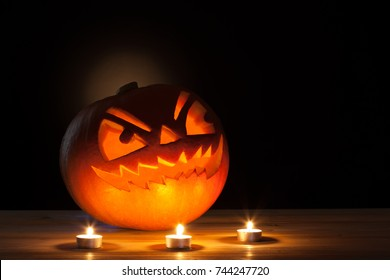 Halloween pumpkin with three candles on wooden table.