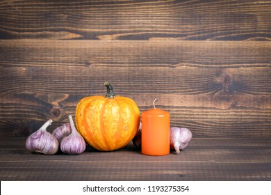 Halloween pumpkins, candle and garlic on a wooden background with copyspace