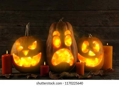 Halloween pumpkins with candles and dry leafs on black background
