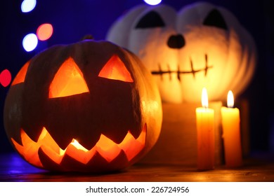 Halloween pumpkins and candles on table on dark color background with multicolor lights