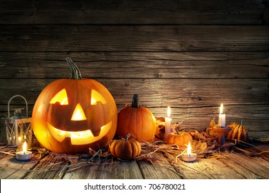 Halloween Pumpkins And Candles On Wooden