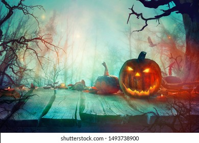 Halloween with Pumpkins and Dark Forest. Scary Jack O' Lantern Halloween Design on Table