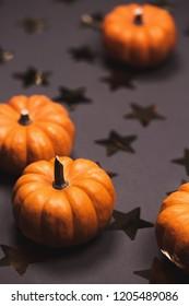 Halloween pumpkins on dark background with stars. Flat lay style.