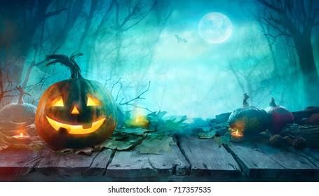 Halloween Kürbis auf Holz. Halloween-Hintergrund im Nachtwald mit dem Mond.