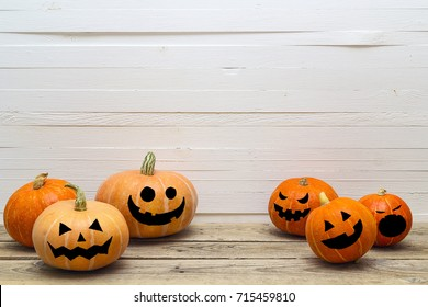 Halloween pumpkins with painted faces on a wooden table on a background of white boards. Halloween background. Space for text.