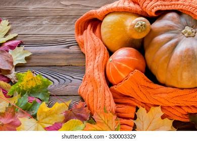 halloween pumpkins shrouded in  cozy orange sweater, fallen leaves on wooden table. top view, copy space