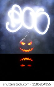 Halloween pumpkins smile and scrary eyes for party night. Close up view of scary Halloween pumpkin with eyes glowing inside at black background. The word Boo is drawn by a light beam