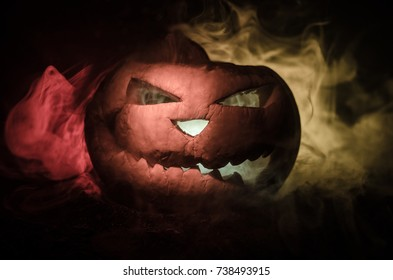 Halloween pumpkins smile and scrary eyes for party night. Close up view of scary Halloween pumpkin with eyes glowing inside at black background. Selective focus