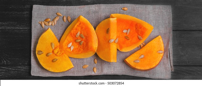 Halloween raw pumpkin pieces cut for baked, napkin tissue, pumpkin seeds on dark black background, top view