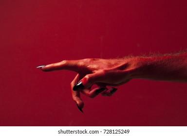 Halloween red devil monster hand with black fingernails against a red background