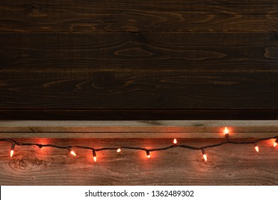 Halloween Rustic Wood Board Shelf and Backdrop with Orange Festive Strand of Lights.  Room or space for copy, text or your words or design element.  Horizontal and wide.