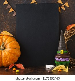 Halloween sale mockup concept with pumpkin, red and yellow leaves and sweet treats: candy and colored cupcake with witch hat. Copyspace.
