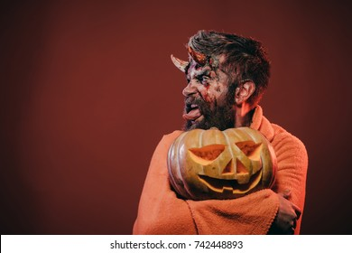 Halloween satan show tongue with horns, beard, blood, wounds. Man devil hold pumpkin on brown background. Darkness and light concept. Demon in blanket with jack o lantern. Trick or treat, copy space