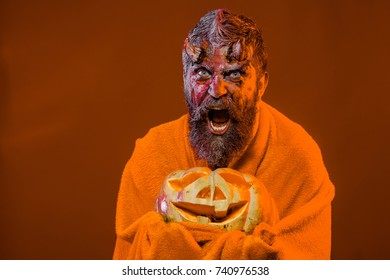 Halloween satan surprised with bloody horns, beard, blood, wounds. Man devil hold pumpkin on orange background. Trick or treat. Darkness and light concept. Demon in blanket with jack o lantern.