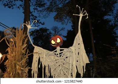 Halloween scarecrow with a carved pumpkin head, white shirt. Scarecrow at night