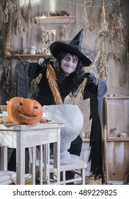 Halloween scary, ugly , funny witch preparing potion in the boiler, pumpkin on the table