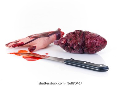 Halloween scene, cut out heart, hand and bloody knife. Studio, white background.