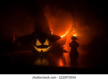 Halloween scene with pumpkin and oil lamp. .Happy Halloween holiday background with old vintage oil lamp on dark toned foggy background. Space for text