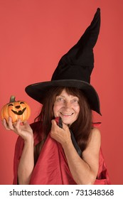 Halloween senior lady with long hair in witch hat. Woman smiling with pumpkin on red background. Trick or treat. Evil spell and magic. Holiday celebration concept.