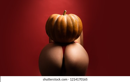 Halloween sexy concept. Big ass for sex celebration. Big ass in intine pose for kamasutra. Hallowen sexy party. Pumpkin on naked big ass. Intime point on woman body. Nightlife and party