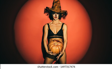 Halloween sexy Witch with a carved Pumpkin on red backgroung. Fantasy horror Halloween. Design for Halloween banner. Beautiful woman posing with pumpkinn