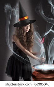 halloween shot of a young and beautiful witch wearing a huge black and orange hat making a poison in a big pot