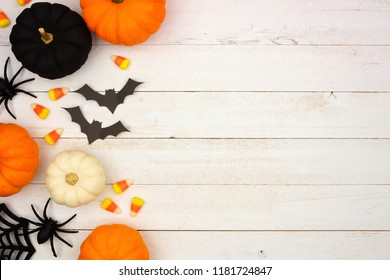 Halloween side border with black, orange and white decor and candy over a white wood background. Top view with copy space.