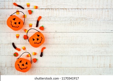 Halloween side border with Jack o Lantern pails and spilling candy. Above view on a white wood background. Copy space.