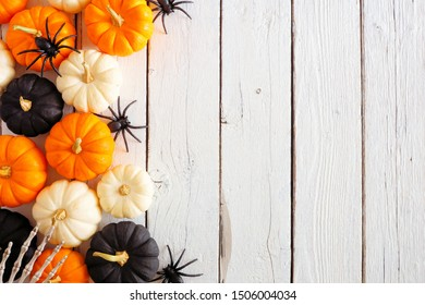 Halloween side border of orange, black and white pumpkins, bones and spiders against a rustic white wood background. Copy space.