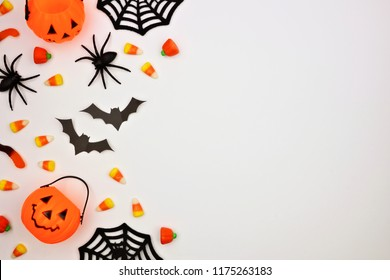 Halloween side border of scattered candy and decor. Flat lay over a white background. Copy space.