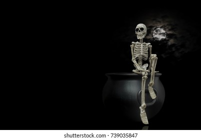 Halloween skeleton sitting on top of a witches cauldron under a nice night moon with dark clouds.