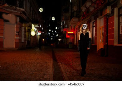 Halloween skull make up girl wear in black at night street of city.
