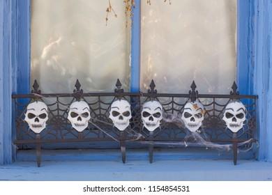 Halloween skulls decorate blue window sill