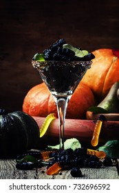 Halloween still life with black candy and pumpkin guards ol old wooden background,  selective focus