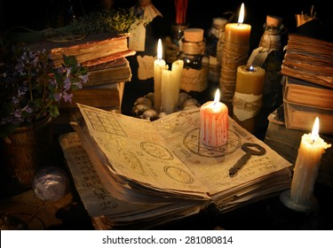 Halloween still life with burning candle on witch book and magic objects in candle light.  Signs on pages of the open book are not foreign text, these letters are imaginary, fictional symbols only.