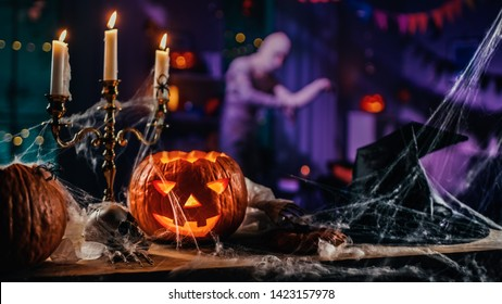Halloween Still Life Colorful Theme: Scary Decorated Dark Room with Table Covered in Spider Webs, Burning Pumpkin, Candlestick, Witch's Hat and Skeleton. In Background Silhouette of Monster Walking By